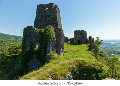 An abandoned fortress in the mountains, overgrown with grass against the background of mountains and sky, Georgia. Abandoned fortress in the mountains.