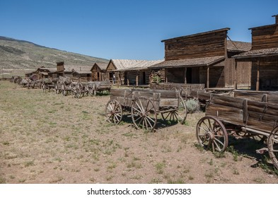Abandoned ghost town in the American wild west. Restored log buildings with a wooden wagon, wagon wheels boardwalk in Cody Wyoming. Abandoned buildings from a western town.