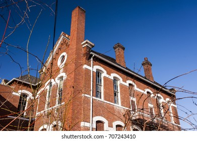 An abandoned, historic school, adorned with red brick and white lintels, is viewed on a sunny evening.