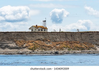 Abandoned house and communication tower on the edge of an island bluff that eroding and falling into the Salish Sea, San Juan Islands, calm sea and cloudy day, USA