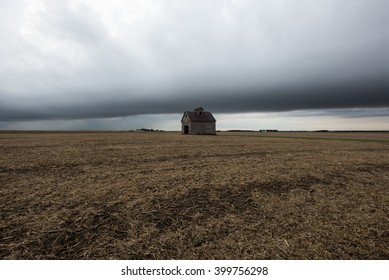 An abandoned house in the middle of a harvested field with a storm front in the distance.