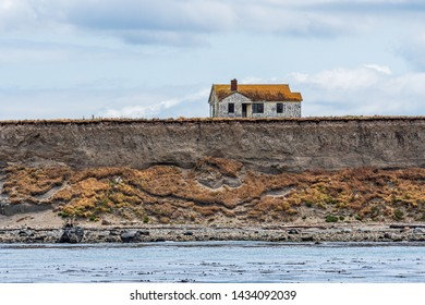Abandoned house on the edge of an island bluff that eroding and falling into the Salish Sea, San Juan Islands, calm sea and cloudy day, USA