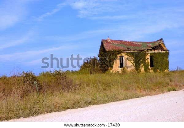 An abandoned house on the side of a country road.