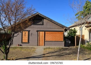 An abandoned house in a poor neighborhood has been boarded up until the bank can dispose of the property