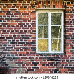 Abandoned house window with red brick wall