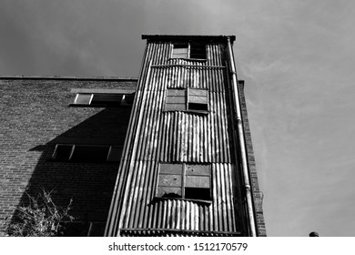 An abandoned industrial building with rusting corrugated metal cladding
