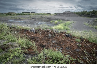 Abandoned industrial land in region of heavy industry with remains of burnt tyres in foreground, UK