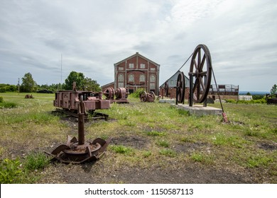 Abandoned Industrial Site. Mining machinery abandoned in a field at the Quincy Mine in the Keweenaw National Historical Park in Calumet, Michigan