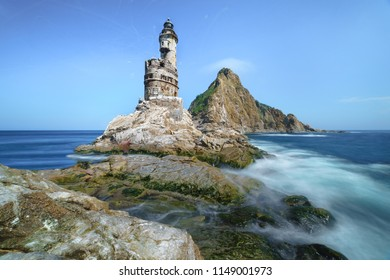 Abandoned Japanese lighthouse on the rock in the south of Sakhalin Island, Russia.
