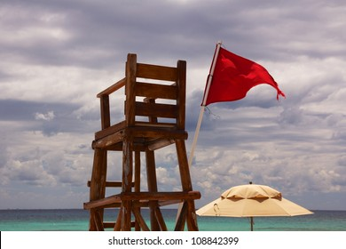 Abandoned lifeguard chair at a Caribbean beach, with the horizon over the ocean in the background and a red flag showing unsafe conditions, under a cloudy sky.
