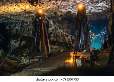 Abandoned limestone underground cave with old wooden bridge and candle illumination, toned