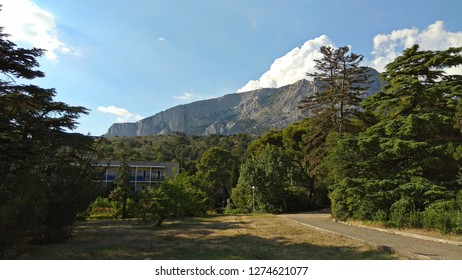 Abandoned, lush park with a mountain ridge view behind the thick trees crowns covering a view of a dilapidated building of the Soviet times. Pavement aside a sunburnt brown lawn in a picturesque park.