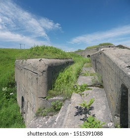 Abandoned Mighty Thick Concrete Breastwork and fortified wall of old Vladivostok Fortress, overgrown with green grass, on sunny day,  Vladivostok, Russia