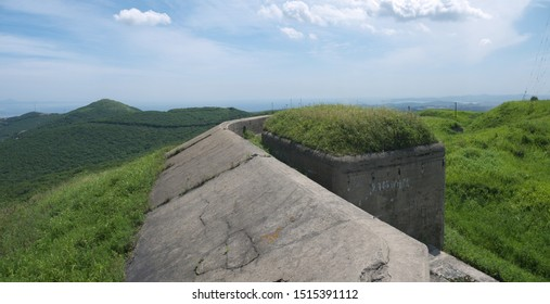 Abandoned Mighty Thick Concrete Breastwork and fortified wall of old Vladivostok Fortress, overgrown with green grass, on sunny day,  Vladivostok, Russia, panoramic view