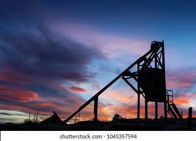 Abandoned Mine Head Frame over Shaft in Nevada Desert at Sunset