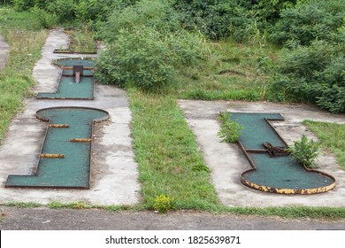 Abandoned mini golf course in a bankrupted resorts with decaying and rusting golf holes.