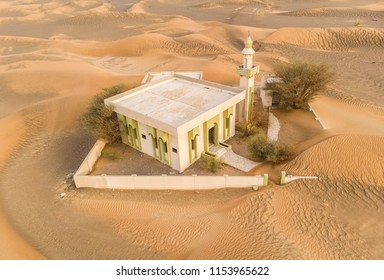 abandoned mosque in a desert, being overtaken by sand