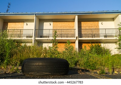 Abandoned Motel in Midwestern small town with tire and overgrown weeds.  Peru, Illinois, U.S.A..