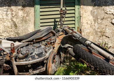 Abandoned motorcycle with scrap and rusted parts in a rural locations - Italy