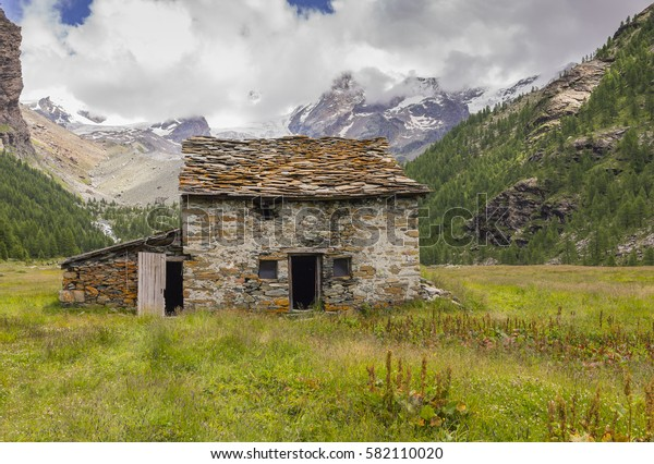 Abandoned mountain hut at high altitude (2,069 m - 6,788 ft) in the Monte Rosa Massif (Ayas Valley, Italy).
