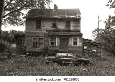 Abandoned and neglected old farmhouse with an abandoned car parked next to it. Fall season. Black and white. Slight sepia.