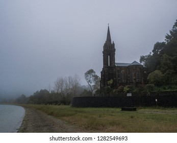 Abandoned Neogothic Chapel of Nossa Senhora das Vitorias at Furnas Lake bank in misty day, Sao Miguel, Azores, Portugal