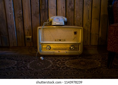 Abandoned nostalgic old style dial telephone and vintage radio on a wooden dark background.
