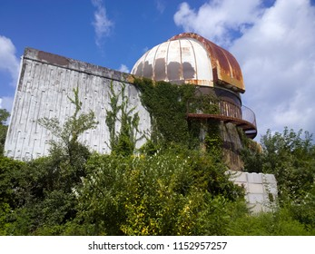 Abandoned observatory overrun by advancing vegetation under the clouds and blue sky