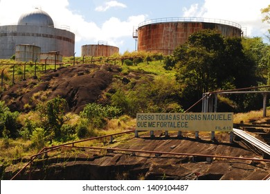 "Abandoned Oil Tanks on Hill. Note: Sign on top of rock reads saying from the Bible in Portuguese: ""I can do all this through Him who gives me strength."" Philippians 4:13"