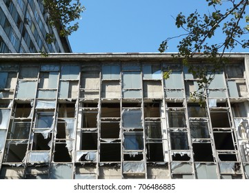 Abandoned old building with broken windows on blue sky background. Holes in the glass by a bullet shot during war shooting. Dirty window frames. Low angle view.