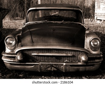 An abandoned old car. Sepia toned.