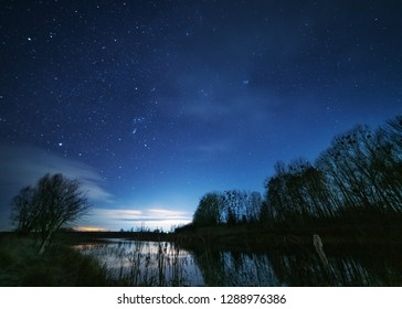 Abandoned old cars, against the background of the night sky with millions of stars around, near the picturesque lake.