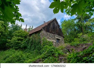 Abandoned old cottage in the woods. Built of stone and wood.