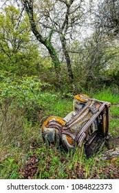 abandoned old furniture among woods