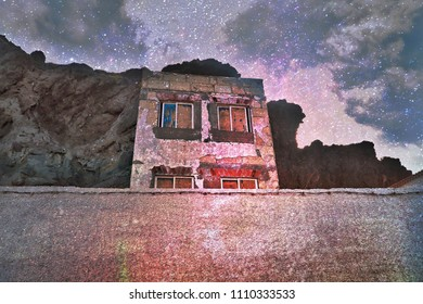 Abandoned, old house  on the rock of the lava on Tenerife. The windows are boarded up. The plaster collapsed. In the evening light, slightly illuminated in purple, creates a ghost Representation.