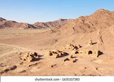 Abandoned old Iranian village in the desert near the city of Yazd, made of clay walls and clay houses, half destroyed, surrounded by rocky mountain hills taken during a dry summer afternoon.