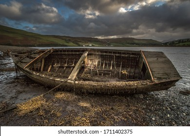 Abandoned old rowing boat at side of loch