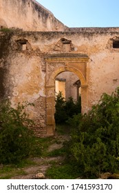 Abandoned old ruined building. Gate with an arc without door. Ruined facade of the walls. Dar Caid Hadji (Hajji), Morocco.