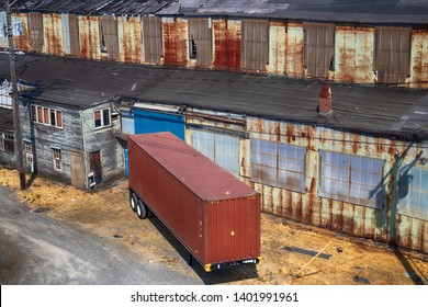 Abandoned old rusty warehouse building with semi tractor trailer parked at door in daylight