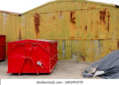 Abandoned old rusty warehouse building with bright red dumpster