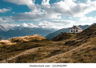 Abandoned old shelter for hikers in the solitude of the high Swiss Alps near Brig in Wallis. With an evening view of the surrounding mountain peaks.