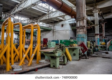 Abandoned old tire factory with rusted machine tools.
