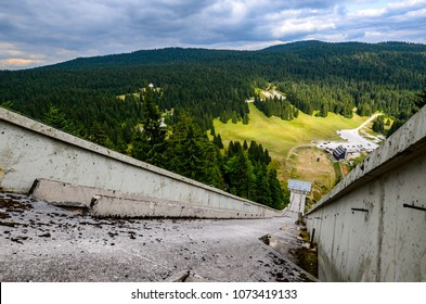 Abandoned olympic ski jump in Sarajevo (Bosnia) from the top. Mountain with forest in background.