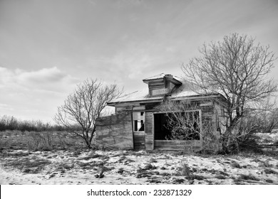 Abandoned one room school house on the prairies in black and white