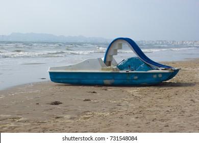 Abandoned paddle boat on beach