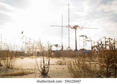 Abandoned Parking Lot With Cranes and Amusement Rides in the Background
