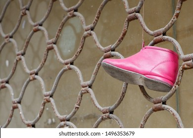 Abandoned pink little girl shoe left on a rusty metal fence depicting a lost childhood or an accident or a sign of rebellion