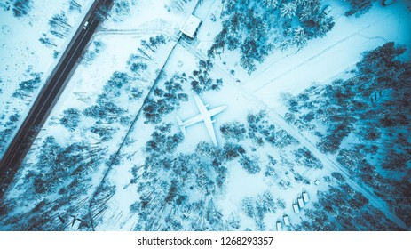 Abandoned plane in frozen forest drone view