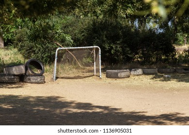 Abandoned poor rural stadium, trampled bald head in a rustic abandoned football field with a gate. Bad field pitchel with hockey gates in an abandoned park. Trampled grass on the football field