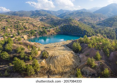 Abandoned pyrite mine in Xyliatos, Cyprus. Lake in open mine pit and waste heaps over mountains landscape